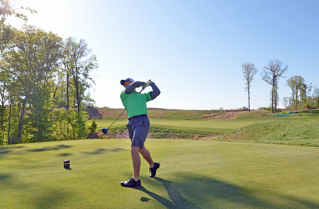 Army veteran Nick McCormick takes the first swing at the grand opening of the Potomac Shores Golf Club in Prince William County, Va., on Monday, May 5, 2014.